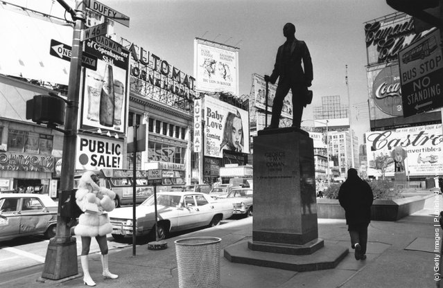 1969:  Times Square, New York with the statue of theatrical impresario, George Cohan being studied by a fur coated, mini-skirted passer-by