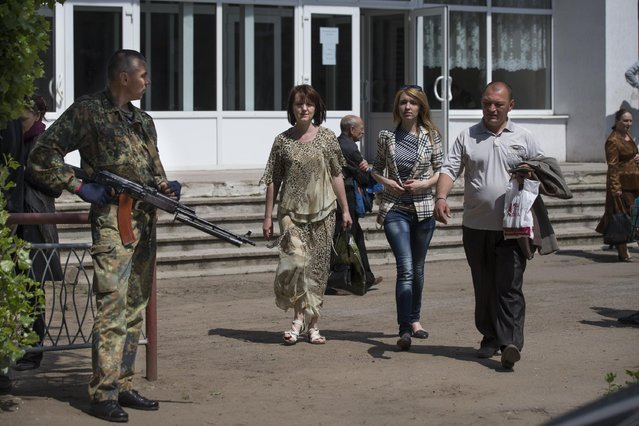 A gunman stands guard as local residents walk from a polling station in Slovyansk, eastern Ukraine, Sunday, May 11, 2014. Residents of two restive regions in eastern Ukraine engulfed by a pro-Russian insurgency cast votes Sunday in contentious and hastily organized independence referendums, which have been rejected as illegal by the Ukrainian government and the West. (Photo by Alexander Zemlianichenko/AP Photo)