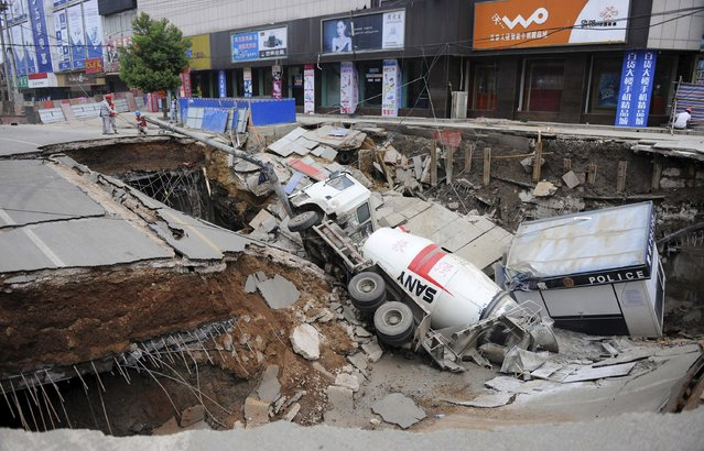 Workers work next to a pit after a truck and a police kiosk fell into a cave-in on a street in Dingyuan county, Anhui province, China, July 14, 2015. The area of the cave-in, which occurred on Monday morning, is around 100 square metres (1,076 square ft). Three people were injured in the incident, according to local media. (Photo by Reuters/Stringer)