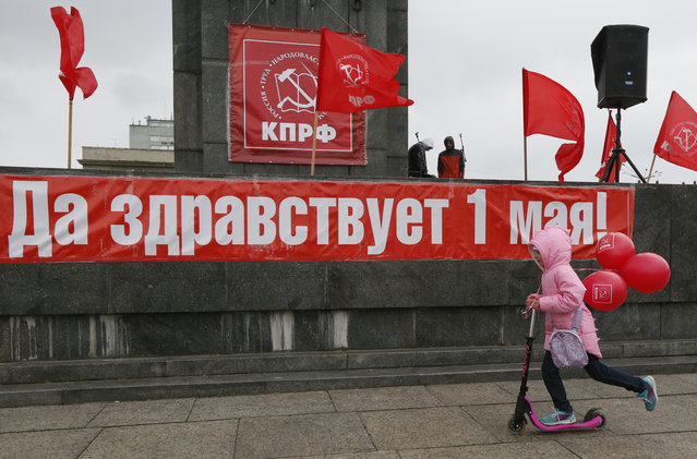 """A child rides a scooter before a May Day rally held by Russian Communist party in central Krasnoyarsk, Siberia. The banner reads, """"Long live May 1!"""" on May 1, 2017. (Photo by Ilya Naymushin/Reuters)"""