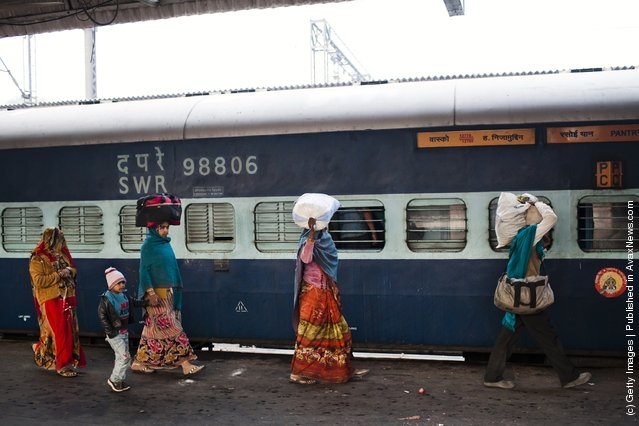 Families alight from a train at the Nizamuddin Railway Station in New Delhi, India