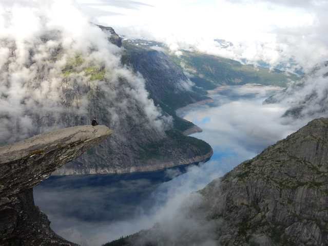 Taking it all in at Trolltunga, a piece of rock which juts horizontally out of a mountain, 700 metres above lake Ringedalsvatnet in Norway. (Photo by Sam Rogers/GuardianWitness)
