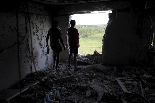 Local residents look through a hole in a damaged multi-storey building, which according to locals was caused by recent shelling, in Avdiivka in Donetsk region, Ukraine, July 18, 2015. (Photo by Maksim Levin/Reuters)