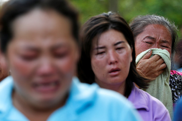 Women who lost their relatives cry near a burnt building at the Pitakiatwittaya School in the northern province of Chiang Rai, Thailand, May 23, 2016. (Photo by Athit Perawongmetha/Reuters)
