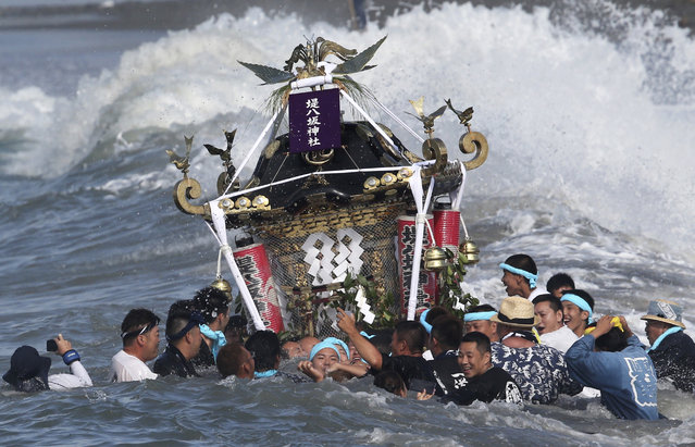 Participants carry a portable shrine, or mikoshi, into the sea during a purification rite at the annual Hamaori Festival in Chigasaki, west of Tokyo early Monday, July 20, 2015. The festival originated from an old times' story about a shrine that was washed away by flood and later found by fishermen. (Photo by Koji Sasahara/AP Photo)