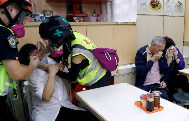 "People receive help from first aid volunteers after the police fired tear gas to disperse anti-government protesters, at a restaurant during a march billed as a global ""emergency call"" for autonomy, in Hong Kong, China on November 2, 2019. (Photo by Tyrone Siu/Reuters)"