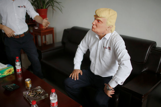 The manager of Jinhua Partytime Latex Art and Crafts Factory wears a mask of U.S. Republican presidential candidate Donald Trump as he poses after talking to reporters in Jinhua, Zhejiang Province, China, May 25, 2016. There's no masking the facts. One Chinese factory is expecting Donald Trump to beat his likely U.S. presidential rival Hilary Clinton in the popularity stakes. (Photo by Aly Song/Reuters)