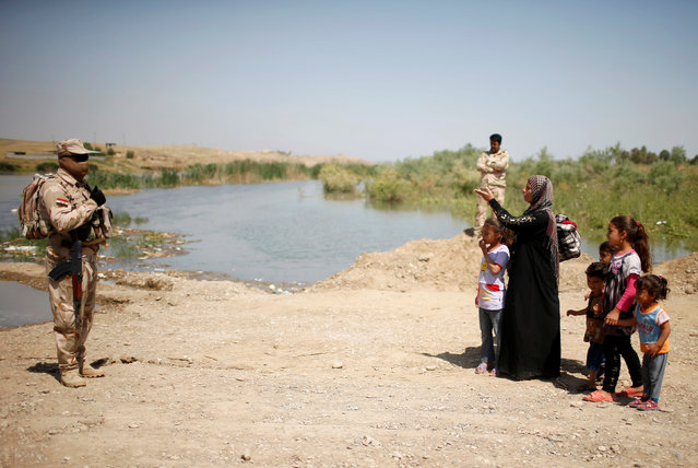 Iraqi woman Lila Ayed, 37, whose husband was killed and two of her daughters went missing during the fighting in Mosul, waits with her children to cross the Tigris river by a military boat after the bridge has been temporarily closed, south of Mosul, Iraq May 4, 2017. (Photo by Suhaib Salem/Reuters)