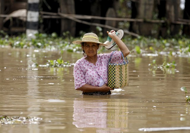 A woman wades through a flooded road in a village at Kawlin township, Sagaing division, Myanmar July 23, 2015. Heavy rains caused flooding over 20,000 acres of rice field and in about a hundred villages, killing at least eight people, according to local media. (Photo by Soe Zeya Tun/Reuters)