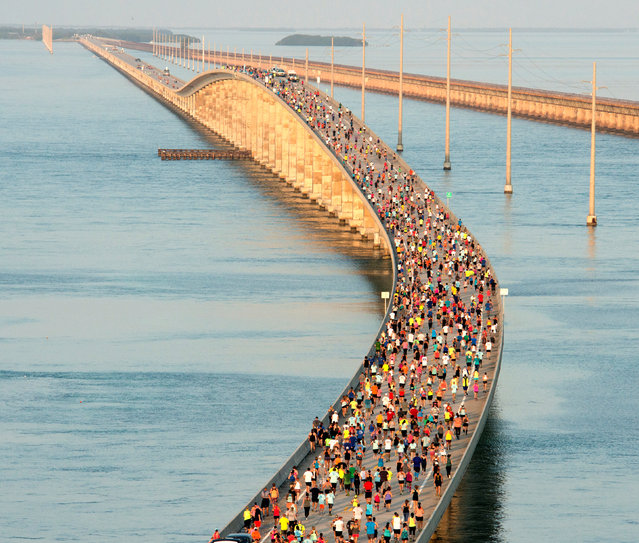 A portion of the field of 1,500 runners compete in the Seven Mile Bridge Run over the longest of 42 bridges on the Florida Keys Overseas Highway near Marathon, Florida, U.S., April 1, 2017. The race was begun in 1982 to mark the completion of a federally funded program to build a then-new Seven Mile Bridge and three dozen other bridges that replaced spans built in the early 1900s. (Photo by Andy Newman/Reuters/Florida Keys News Bureau)