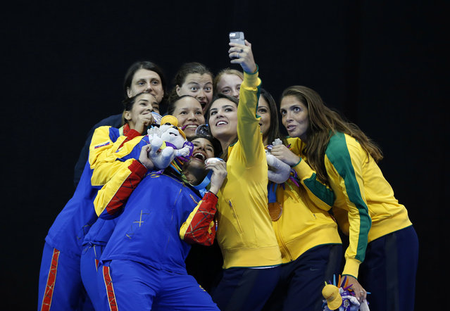 Medalists in the women's epee team fencing competition pose together for a selfie on the medals podium at the Pan Am Games in Toronto, Friday, July 24, 2015. Included are U.S. gold medalists Katharine Holmes, Katarzyna Trzopek, and Anna Catherine Van Brummen; Venezuelan silver medalists Eliana Lugo, Dayana Martinez, and Maria Martinez; and Brazilian bronze medalists Rayssa Costa, Nathalie Moellhausen, and Amanda Simeao. (Photo by Rebecca Blackwell/AP Photo)
