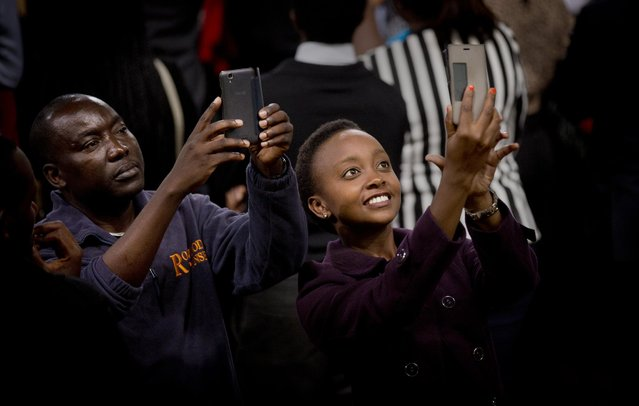 Members of the audience take selfies as President Barack Obama gives a speech behind them, at the Safaricom Indoor Arena in the Kasarani area of Nairobi, Kenya Sunday, July 26, 2015. Obama is traveling on a two-nation African tour where he will become the first sitting U.S. president to visit Kenya and Ethiopia. (Photo by Ben Curtis/AP Photo)