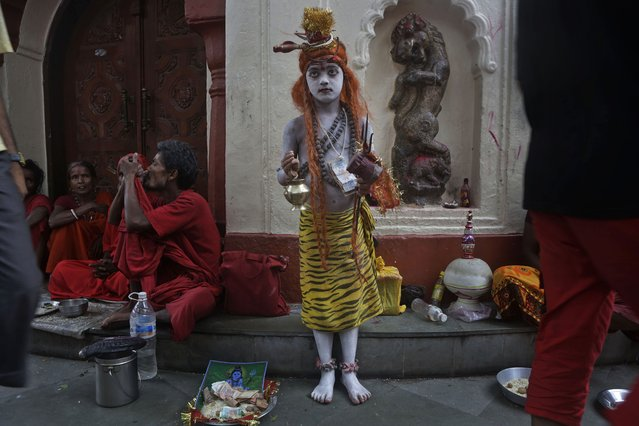 An Indian boy stands dressed like Hindu god Shiva to attract alms from devotees as a man smokes marijuana, left, during the Ambubasi festival at the Kamakhya Hindu temple in Gauhati, India, Sunday, June 22, 2014. The annual festival where hundreds of holy men from an esoteric form of Hinduism, gather to perform rituals at the temple began Sunday. (Photo by Anupam Nath/AP Photo)