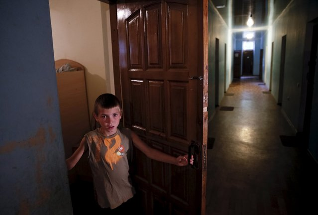 A boy looks out from a room inside a building on the compound of a health and rest centre temporarily serving as accommodation for refugees from the eastern regions of the country in the town of Korostyshiv, Zhytomyr region, Ukraine, July 30, 2015. (Photo by Valentyn Ogirenko/Reuters)
