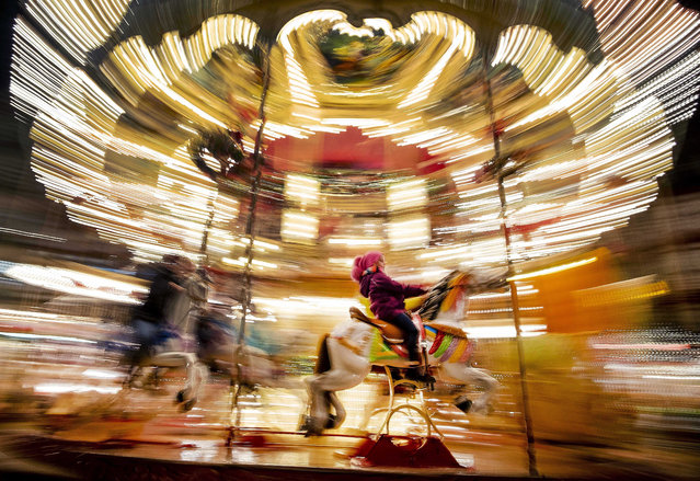 A girl rides a horse on a merry-go-round on the Christmas market in Frankfurt, Germany, Monday, December 16, 2019. (Photo by Michael Probst/AP Photo)