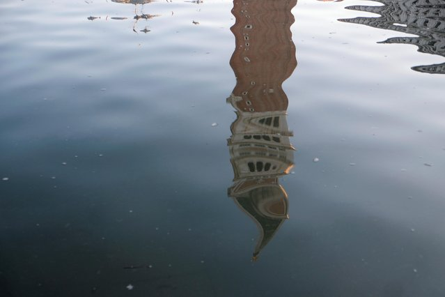 St. Mark's bell tower (Campanile) is reflected in the water during high tide in Venice, Italy on December 24, 2019. (Photo by Manuel Silvestri/Reuters)