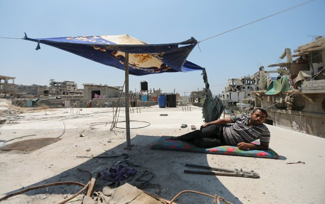 A Palestinian man rests atop the roof of his house that witnesses said was damaged by Israeli shelling during a 50-day war last summer, in the east of Gaza City May 6, 2015. (Photo by Mohammed Salem/Reuters)