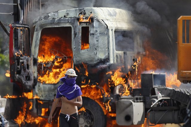 A masked demonstrator walks near a flaming truck, seized and set on fire by demonstrators, during an anti-government protest on the Francisco Fajardo highway, outside La Carlota Air Base in Caracas, Venezuela, Friday, June 23, 2017. More than 70 people have been killed during almost 90 days of protests seeking President Nicolas Maduro's removal. (Photo by Ariana Cubillos/AP Photo)