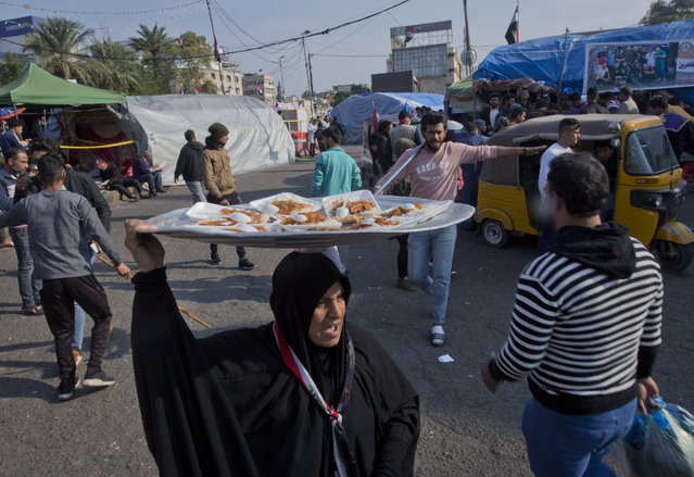 In this photo taken Monday, December 9, 2019, a volunteer woman distributes free meals of the popular dish of Tepsy, a mix of vegetables in red souse served with rice, to protester in the center of Baghdad, Iraq. (Photo by Nasser Nasser/AP Photo)