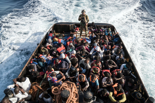 A Libyan coast guardsman stands on a boat during the rescue of 147 illegal immigrants attempting to reach Europe off the coastal town of Zawiyah, 45 kilometres west of the capital Tripoli, on June 27, 2017. More than 8,000 migrants have been rescued in waters off Libya during the past 48 hours in difficult weather conditions, Italy's coastguard said on June 27, 2017. (Photo by Taha Jawashi/AFP Photo)