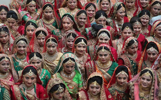 Indian brides wait for their ceremony at a mass wedding in Surat, India, Saturday, December 21, 2019. More than a hundred couples tied the knot at the mass wedding. Weddings in India are expensive affairs with the bride's family traditionally expected to pay the groom a large dowry of cash and gifts. (Photo by Ajit Solanki/AP Photo)