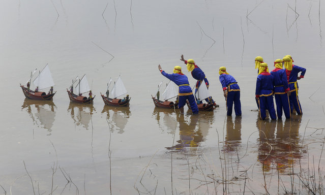 Fishermen from Ly Son island release miniature fishing boat models with artificial soldiers into the water during a re-enactment of the Khao Le The Linh ceremony at a Vietnam Cultural village in Dong Mo, outside Hanoi June 29, 2014. (Photo by Reuters/Kham)