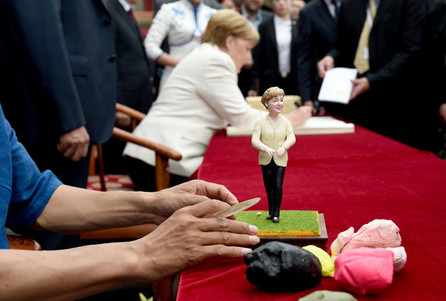 German Chancellor Angela Merkel writes in a book near a figurine of herself, near the Shenyang Imperial Palace, China, 14 June 2016. Merkel is on an official visit to the Asian nation. (Photo by Rainer Jensen/EPA)