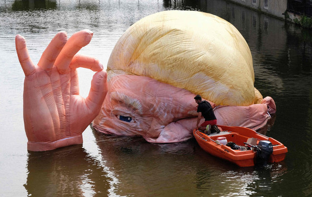"""A picture taken on July 5, 2019 shows the installation """"Everything is fine"""" depicting the half submerged head of US President Donald Trump by Jacques Rival, architect, displayed in the Moselle river as part of the digital art festival """"Constellations de Metz"""" in Metz, eastern France. """"Constellations de Metz"""" is a digital arts festival that runs from June 20 to September 7, 2019 and focuses on showcasing the area's urban spaces and heritage. (Photo by Jean-Christophe Verhaegen/AFP Photo)"""