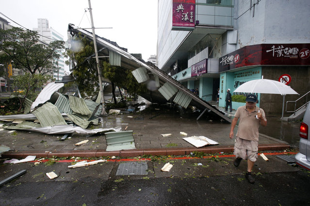 A man passes a damaged structure from Typhoon Soudelor in Taipei, Taiwan, Saturday, August 8, 2015. Soudelor brought heavy rains and strong winds to the island Saturday with winds speeds over 170 km per hour (100 mph) and gusts over 200 km per hour (120 mph) according to Taiwan's Central Weather Bureau. (Photo by Wally Santana/AP Photo)