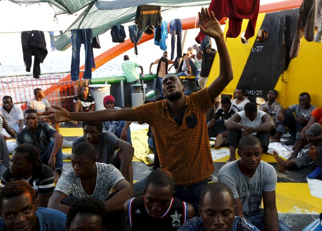 Migrants take part in an impromptu prayer meeting at the stern of the Medecins sans Frontieres (MSF) rescue ship Bourbon Argos somewhere between Libya and Sicily, August 8, 2015. Some 241 mostly West African migrants on the ship are expected to arrive on the Italian island of Sicily on Sunday morning, according to MSF. (Photo by Darrin Zammit Lupi/Reuters)
