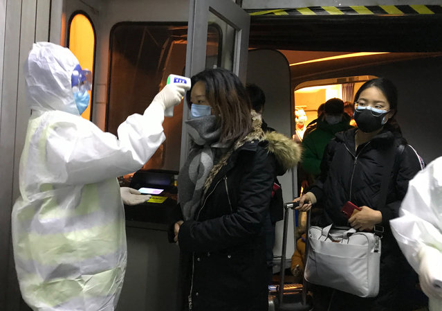 Health Officials in hazmat suits check body temperatures of passengers arriving from the city of Wuhan Wednesday, January 22, 2020, at the airport in Beijing, China. Nearly two decades after the disastrously-handled SARS epidemic, China's more-open response to a new virus signals its growing confidence and a greater awareness of the pitfalls of censorship, even while the government is as authoritarian as ever. (Photo by Emily Wang/AP Photo)