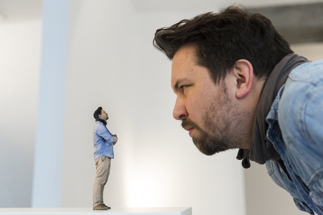 Twinkind co-founder Timo Schaedel looks at a 3D-printed figure of himself at the Twinkind 3D printing studio in Berlin, December 13, 2013. (Photo by Thomas Peter/Reuters)