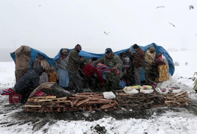 Aymara people prepare offerings during a snowstorm in La Cumbre, near La Paz, August 12, 2015. (Photo by David Mercado/Reuters)