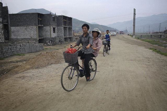 In this Friday, July 21, 2017, photo, women cycle past a construction site on the outskirts of Hamhung, North Korea's second-largest city, where construction workers unearthed a rusted but still potentially deadly mortar round in February. North Korea is just one of many countries still dealing with the explosive legacy of major wars. But the three-year Korean War, which ended in what was supposed to be a temporary armistice on July 27, 1953, was one of the most brutal ever fought. (Photo by Wong Maye-E/AP Photo)