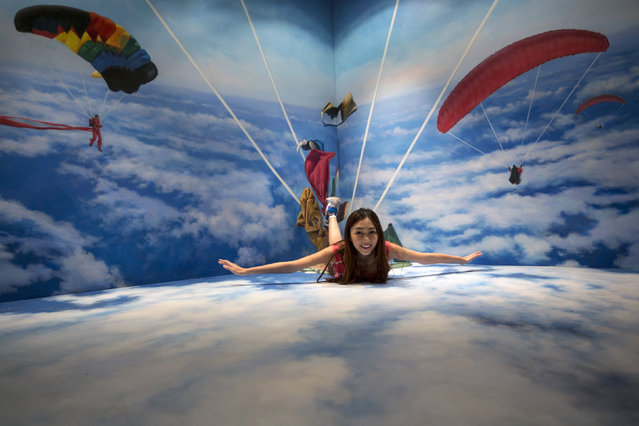 A woman poses for a photograph with a 3D painting at HK 3D Museum in Hong Kong June 26, 2014. (Photo by Tyrone Siu/Reuters)