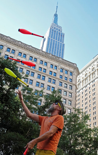 Juggling fanatic Jeff Mitchell practices in Herald Square with the Empire State Building in the background, in the Manhattan borough of New York City, U.S., June 30, 2016. (Photo by Rickey Rogers/Reuters)