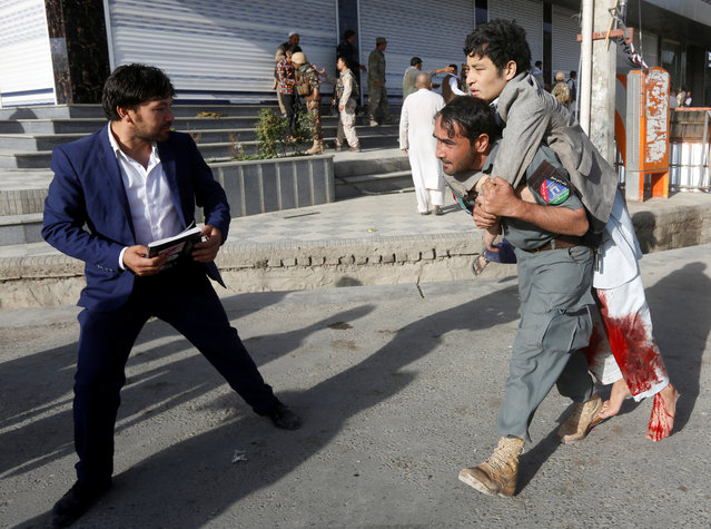 An Afghan policeman carries an injured man after a suicide attack followed by a clash between Afghan forces and insurgents, attack on a Shi'ite Muslim mosque in Kabul, Afghanistan on Friday, August 25, 2017. (Photo by Omar Sobhani/Reuters)