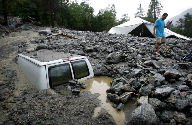 An official of Forest Home Christian Conference Center in Forest Falls, Calif., inspects damage on the property following thunderstorms on Sunday, August 3, 2014. About 1,500 residents of Oak Glen, and another 1,000 residents of Forest Falls in the San Bernardino Mountains were unable to get out because the roads were covered with mud, rock and debris, authorities said. (Photo by David Bauman/AP Photo/The Press-Enterprise)