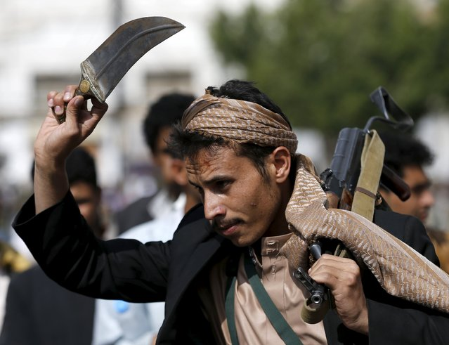 A Houthi follower carries his rifle and waves a dagger as he dances the traditional Baraa dance ahead of a demonstration against the Saudi-led air strikes in Yemen's capital Sanaa August 24, 2015. (Photo by Khaled Abdullah/Reuters)
