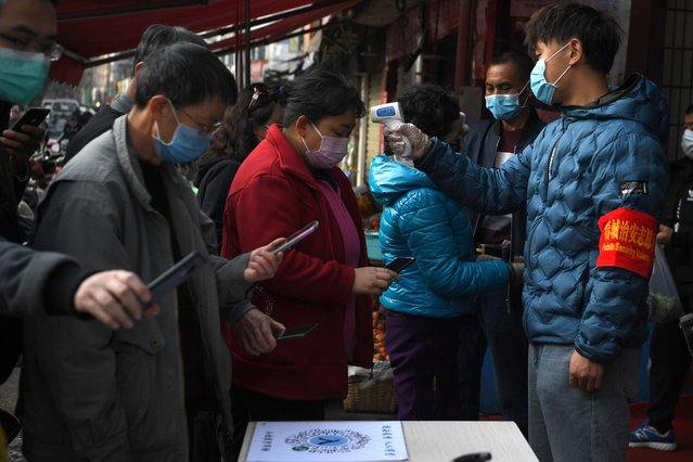 People wearing face masks scan a QR code to submit their personal information while security volunteers check their temperatures at an entrance of a grocery market in Kunming, Yunnan province, China, February 24, 2020. (Photo by Reuters/China Stringer Network)