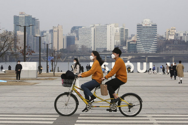A couple wearing face masks rides a bicycle at a park in Seoul, South Korea, Saturday, March 7, 2020. The number of infections of the COVID-19 disease spread around the globe. (Photo by Ahn Young-joon/AP Photo)