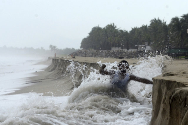 A man fights against waves caused by approaching Hurricane Max that took away part of the beach in Pie de La Cuesta, on the outskirts of Acapulco, Guerrero state, Thursday, September 14, 2017. Max has strengthened into a Category 1 hurricane off Mexico's southern Pacific coast and is forecast to make landfall later Thursday along the coast of Guerrero state. It's a region that includes the resort city of Acapulco. (Photo by Bernandino Hernandez/AP Photo)