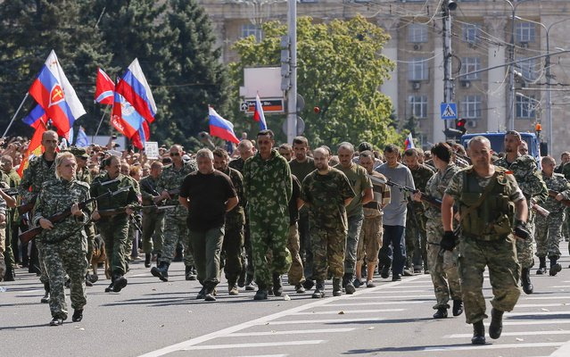 Armed pro-Russian separatists escort a column of Ukrainian prisoners of war (C) as they walk across central Donetsk August 24, 2014. Pro-Russian separatist rebels force-marched dozens of Ukrainian prisoners of war along the main street of the rebel-held Ukrainian town of Donetsk on Sunday. (Photo by Maxim Shemetov/Reuters)