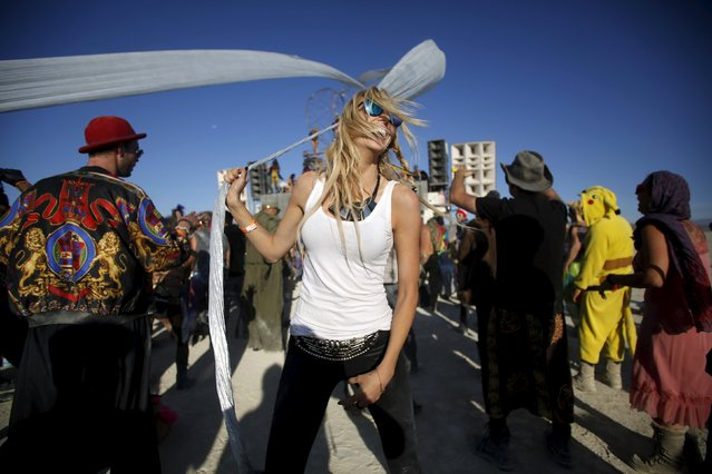 """Lauren Gilligan dances at the Robot Heart during the morning hours at the Burning Man 2015 """"Carnival of Mirrors"""" arts and music festival in the Black Rock Desert of Nevada, August 31, 2015. (Photo by Jim Urquhart/Reuters)"""