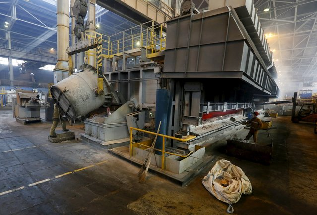 A worker (L) operates a mixer of fused aluminium at the foundry shop of the Rusal Sayanogorsk aluminium smelter outside the town of Sayanogorsk, Russia, September 3, 2015. (Photo by Ilya Naymushin/Reuters)