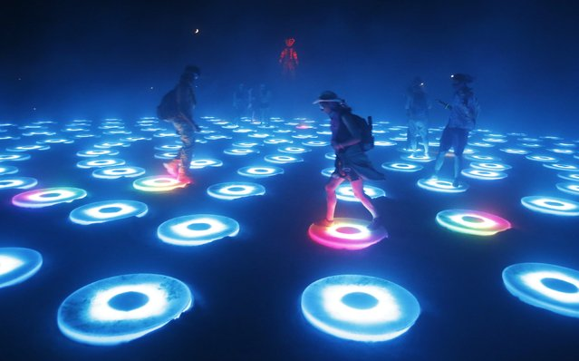 "Participants interact with the art installation The Super Pool during a dust storm at the Burning Man 2014 ""Caravansary"" arts and music festival in the Black Rock Desert of Nevada, August 29, 2014. (Photo by Jim Urquhart/Reuters)"