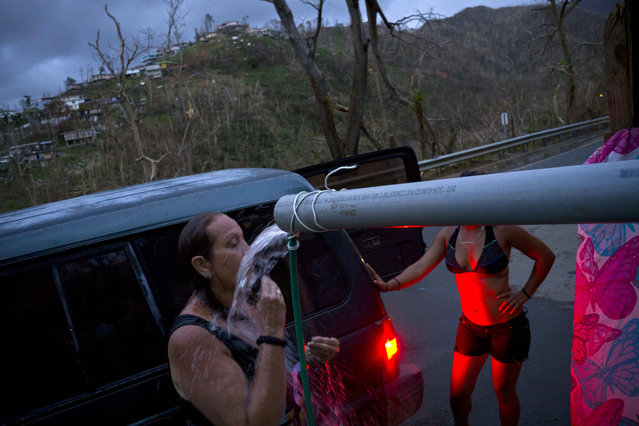 People affected by Hurricane Maria bathe in water piped from a creek in the mountains, in Naranjito, Puerto Rico, Thursday, September 28, 2017. Residents of the area drive to the pipes to bathe because they were left without water supplies by the damage caused by Hurricane Maria. The pipe was set up by a neighbor who ran it from a creek in his property to the side of the road in order to help those left without water. (Photo by Ramon Espinosa/AP Photo)