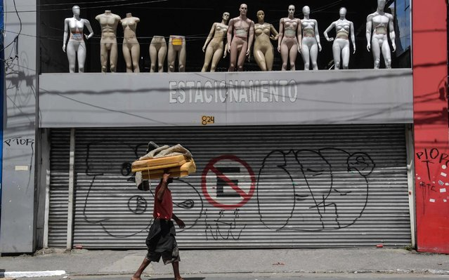 A homeless walks past a closed parking lot and mannequins in downtown Sao Paulo, Brazil, after the city government decreed the closure of shops and stores as a precautionary measure against the spread of the novel coronavirus COVID-19, on March 24, 2020. Latin America's biggest city, the traffic-clogged concrete jungle of Sao Paulo, slowed to an eerily quiet lull Tuesday as it went into partial quarantine in a bid to stop the new coronavirus from ravaging Brazil. (Photo by Nelson Almeida/AFP Photo)