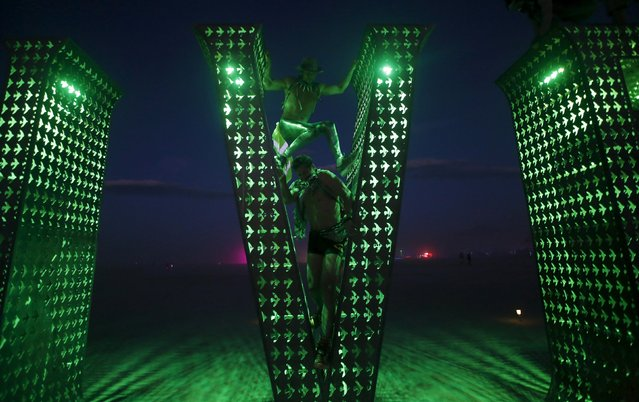 "Participants climb on an art installation during the Burning Man 2015 ""Carnival of Mirrors"" arts and music festival in the Black Rock Desert of Nevada, September 2, 2015. (Photo by Jim Urquhart/Reuters)"