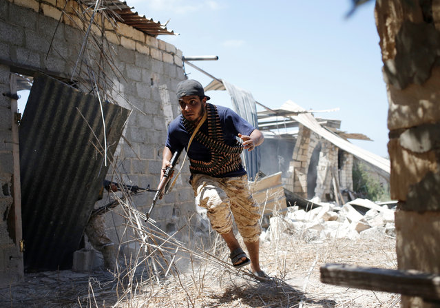A fighter of Libyan forces allied with the U.N.-backed government runs for cover during a battle with Islamic State fighters in Sirte, Libya, July 31, 2016. (Photo by Goran Tomasevic/Reuters)